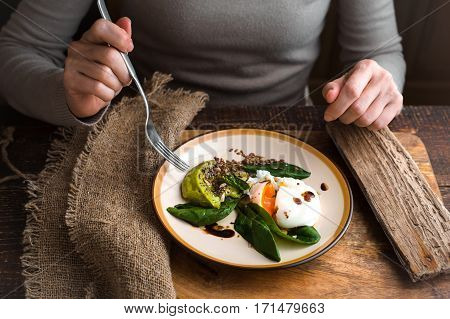 Woman eating poached egg with avocado cream horizontal
