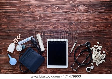 White tablet pc,tonometer,stethoscope,pills,bandage, thermometer and enema on wooden table.