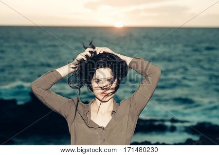 Pretty girl or sexy woman with windy brunette hair poses on blue sea beach at sunset on natural background