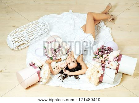 Sexy young pretty woman or cute smiling girl with long hair in white dress laying on bedsheet among lilac rose and peony flower boxes on wooden floor