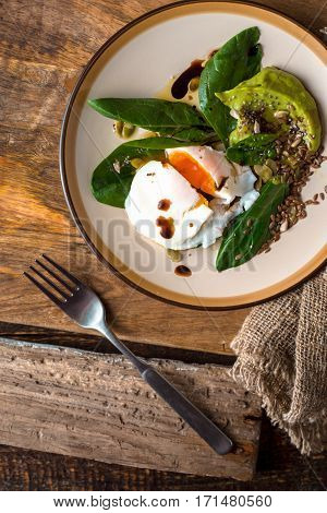 Poached egg with avocado cream and spinach on the old wooden table vertical