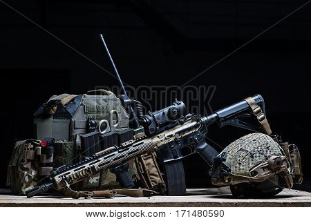 Body armor coverassault rifle with a sight and helmet on black background