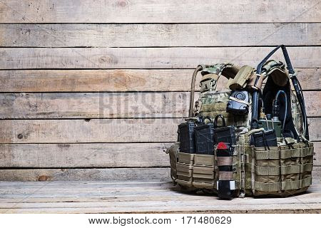 Body armor with ammo and other military equipment on wooden background