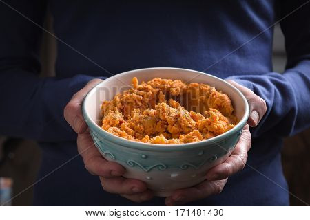 Bowl with hummus on the hands horizontal