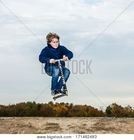 Boy Enjoys Jumping With His Scooter Over A Ramp