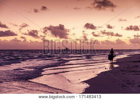 Bavaro beach Dominican republic - January 3 2017: Colorful sunrise over Atlantic ocean coast. Punta Cana resort woman tourist walk on wet sand