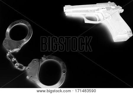 Black and white negative photo of crime symbols handcuffs and gun