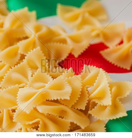 Traditional Italian cuisine. Dry Macaroni close-up on a background of colors of the Italian tricolor