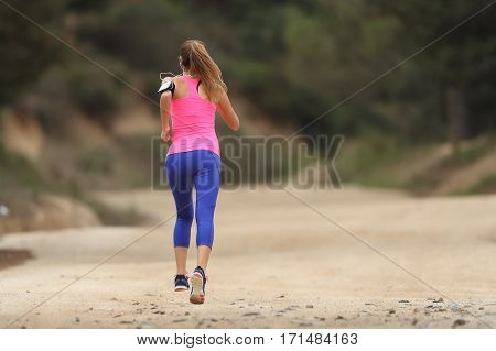Back view of a runner wearing colorful sportswear running in the country