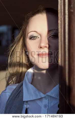 Portrait of young Caucasian Blond Woman Looking Out of the Doorway with Face Half Lit and Partially in Shadow. Vertical Image