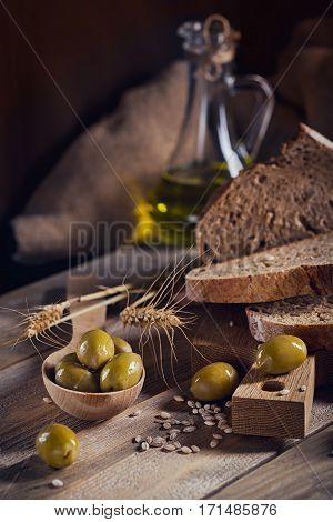 Fresh multigrain crusty bread green olives and wheat ears on a rustic wooden table. Bakery and grocery food store concept.