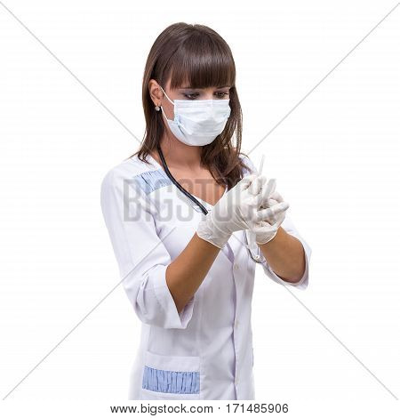 Doctor or nurse in face mask and lab coat holding syringe. Isolated over white.