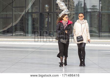 Two Beautiful brunette Women posing On urban background