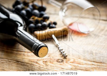 Glass of red wine and bottle with corkscrew and grape on wooden desk background