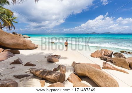 Active sporty man wearing black swimsuit enjoying swimming and snorkeling at amazing on Anse Patates beach on La Digue Island, Seychelles. Summer vacations on picture perfect tropical beach concept.