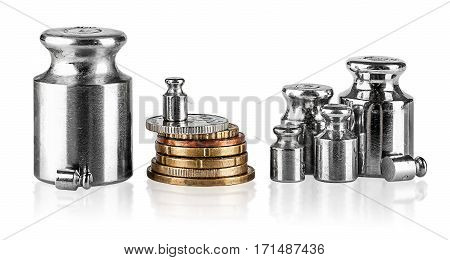 Several old scaling weights and coins isolated on white background