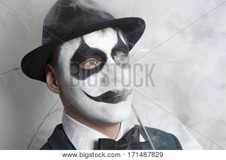Scary evil clown wearing a bowler hat vaping on wall background