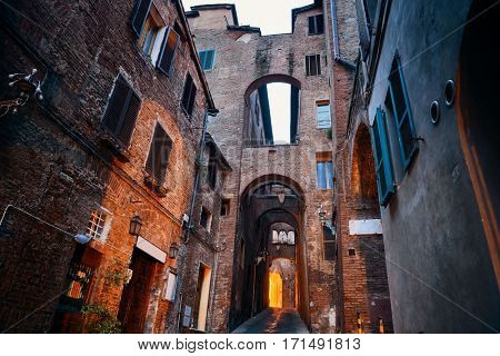 Street view with old buildings and archway in Siena, Italy.