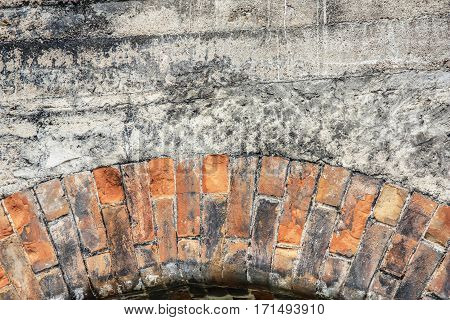Close-up view of cracked old building brick wall with concrete on top background concept