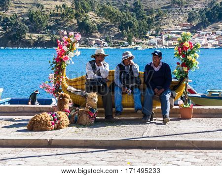 Tiquina, Bolivia - December 7, 2011: Three men sitting on a bench in shade from the bright noon sun, waiting for the ferry