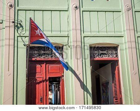 Cuban flag with door and window facade at colonial Cuban house in Santiago de Cuba