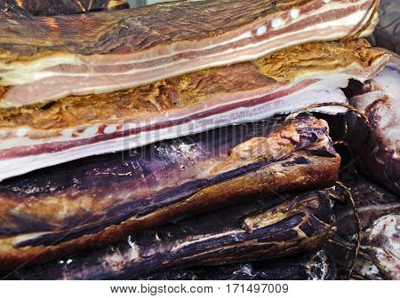 Homemade bacon on the table exposed for sale.