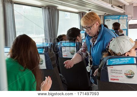 MOSCOW/ RUSSIA - MAY 17. The woman - conductor of a passenger bus sells the tickets on May 17, 2014. Moscow region, Russia.