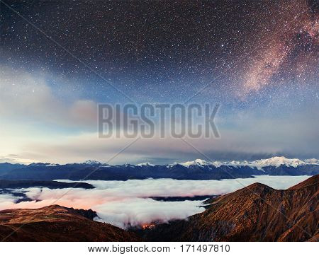 Starry sky above the thick fog on the mountain pass Goulet. Georgia, Svaneti. Europe. Caucasus Mountains