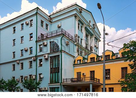 Modern building and old house with a lot of air conditioners on the facades. Ozerkovskiy lane, Moscow, Russia