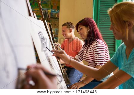 School of art college of arts education for group of young students. Happy latina woman smiling girl learning to paint.