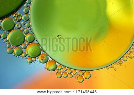 Oil in water forming blue and green circles abstract background
