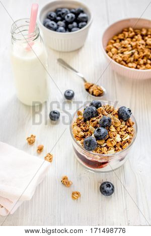 Fitness breakfast with homemade granola from yoghurt and flakes, milk and berries on white desk background