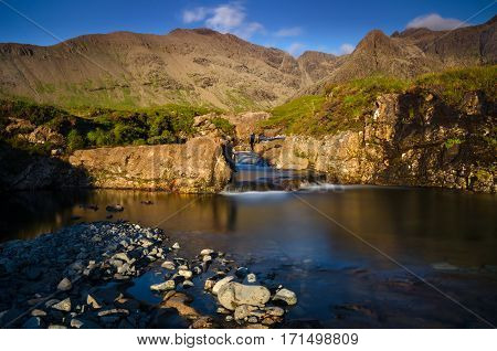 Fairy Pools waterfalls with Cuillin Mountains in sunset light Isle of Skye Scotland