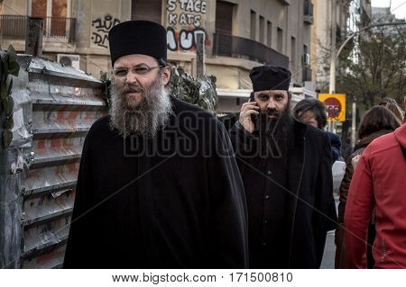 THESSALONIKI GREECE - DECEMBER 24 2015: Two Greek Orthodox priests walking in the streets of Thessaloniki one having a phone call on his smartphone