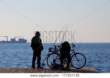 THESSALONIKI GREECE - DECEMBER 25 2015: Silhouette of old fishermen on Thessaloniki seafront on the Aegean sea