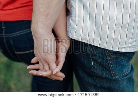 Cropped view of a couple holding hands together