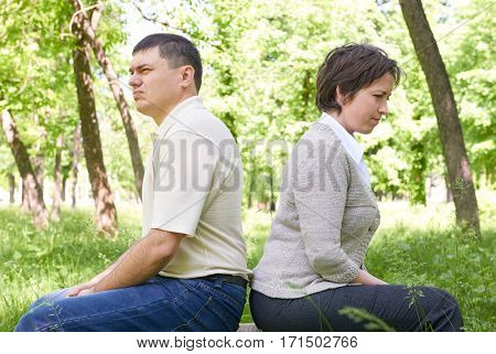 Unhappy couple in summer park. Face expression and grimace.