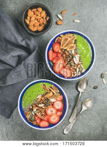Healthy breakfast. Green smoothie bowls with strawberries, granola, chia and pumpkin seeds, dried figs and almonds over grey concrete background, top view. Diet, clean eating, vegan food concept