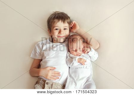older brother hugging his newborn sister. Children in bright clothes on a white blanket.