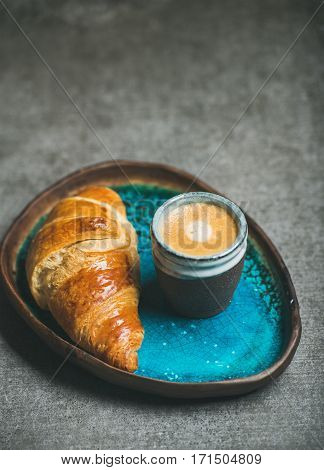 Cup of espresso coffee and croissant in turquoise blue ceramic tray over grey concrete background, selective focus, copy space, vertical composition