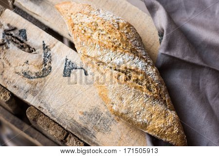 Rye whole wheat bread roll with golden crust dusted with flour on wood vintage box grey linen napkin top view close up