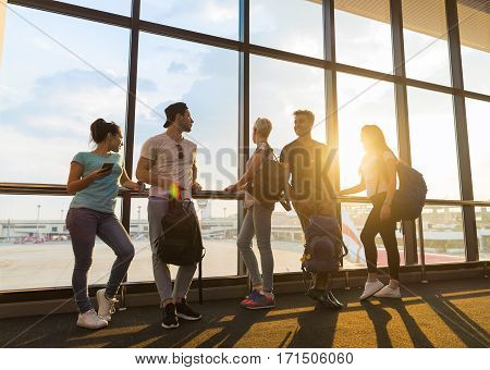 Young People Group In Airport Lounge Near Windows Waiting Departure Speaking Happy Smile Mix Race Friends Flight Delay