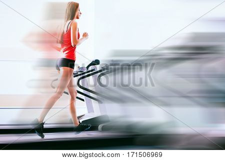 Active young woman running on treadmill at the gym exercising. Run on a machine.