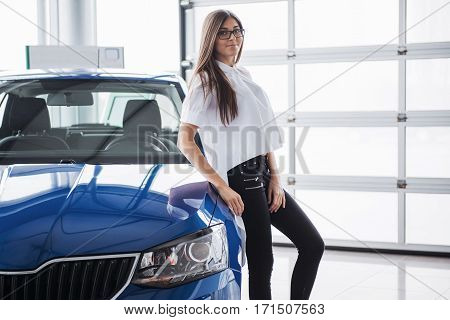 Pretty girl is standing near her car. She is leaning on the roof and is looking aside dreamingly. She is smiling with anticipation