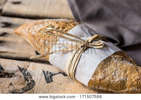 Loaf of rye whole wheat bread wrapped in parchment paper linen napkin vintage wood background top view selective focus poster