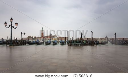 Gondolas by Saint Mark square during  with San Giorgio di Maggiore church in the background in Venice Italy during high tide