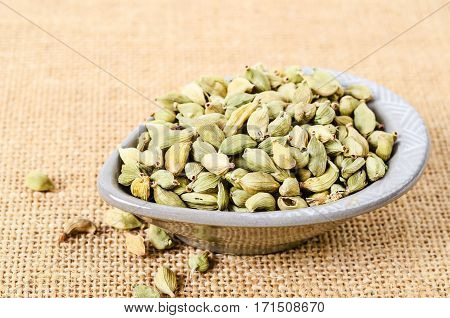 Green cardamon in cup on sack background.