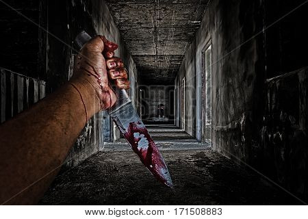 hand holding knife smeared with blood and some people sitting in the room at end of scary hallway walkway in abandoned building.
