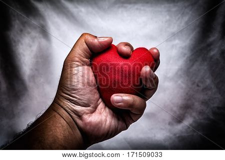 angry man crushing red heart in hand. unrequited love. love concept for valentines day. in dark tone.