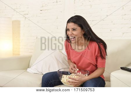 young beautiful and attractive latin woman at home sofa couch laughing and smiling happy watching television comedy movie or funny tv series alone eating popcorn